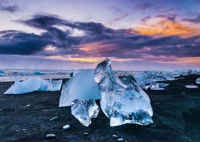 Icebergs On Black Sand At Jokulsarlon Lake Against Sky At Sunrise