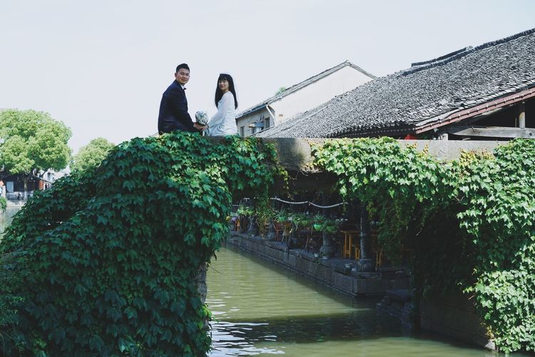 Togetherness Waterfront Green Tree Bridge Sitting Plant Nature Architecture Water Built Structure Leisure Activity Sky Two People Lifestyles Outdoors