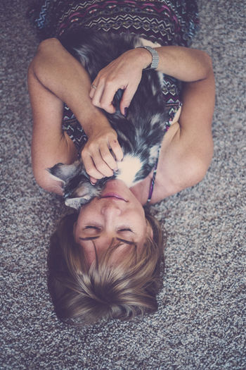 Portrait for a blonde caucasian woman with her cat. Emotion and love for animals Real People Relaxation Lying Down Domestic Pets Mammal High Angle View Domestic Animals People Leisure Activity One Animal Vertebrate Front View Canine Dog Resting Lying On Back Hairstyle Pet Owner Flooring Aerial View Purebred Cat Love Emotions Young Woman
