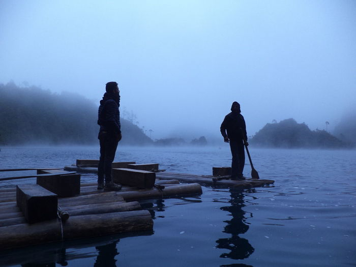 Two men standing on wooden raft at lake against sky during winter