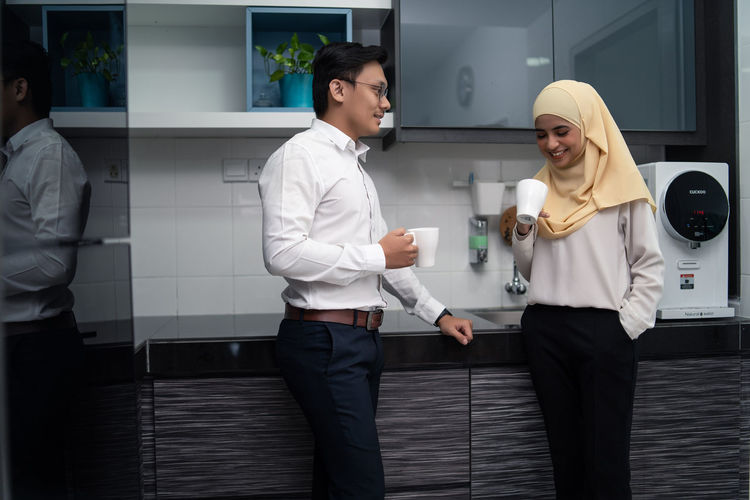 Business People Having Coffee While Standing In Office Cafeteria