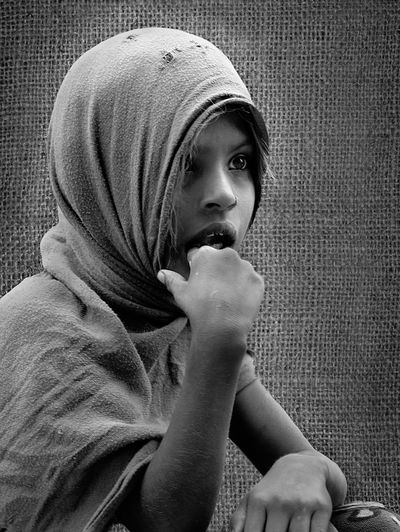 Girl wearing headscarf while looking away by burlap