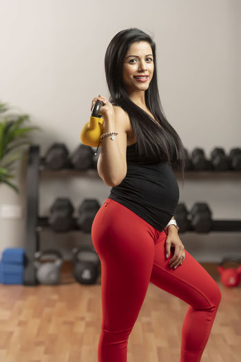 Pregnant Woman Exercising With Kettlebell At Home