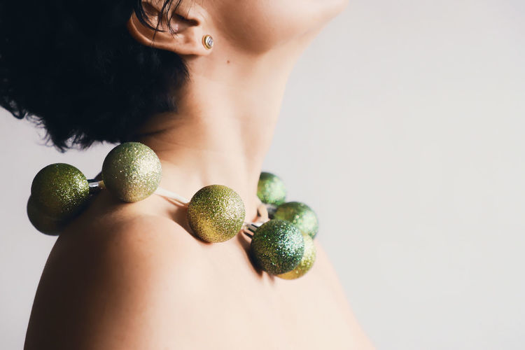 Midsection Of Topless Mature Woman Wearing Green Necklace Against White Background