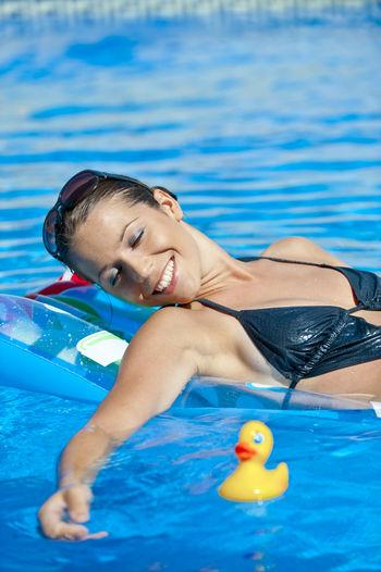 Sensuous Woman Relaxing On Raft In Swimming Pool