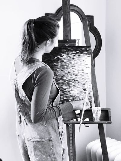 Rear view of woman painting while standing at art studio