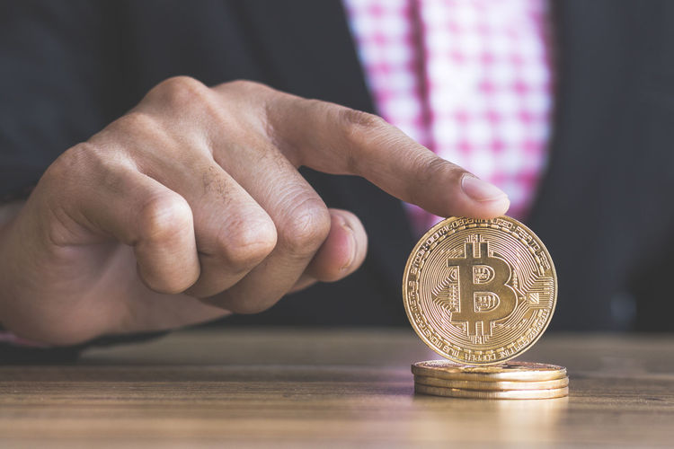 Midsection of businessman holding bitcoins on table