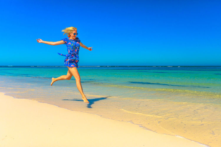 Full length of woman jumping on shore at beach during sunny day