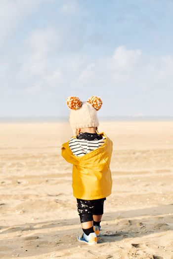 Rear view of baby boy wearing warm clothing standing on beach against sky
