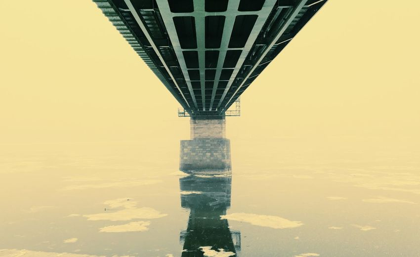Reflection of bridge and buildings in city against sky