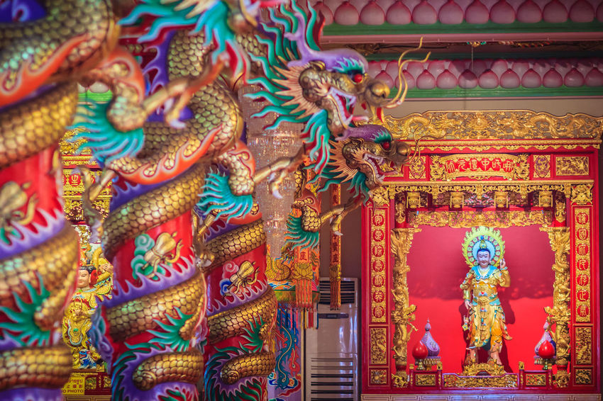 Colorful dragons and statue of Nezha, the protective deity in Chinese folk religion at Chinese public temple. Dragon Animal Representation Architecture Art And Craft Belief Building Building Exterior Built Structure Creativity Multi Colored Nezha No People Ornate Place Of Worship Religion Representation Sculpture Spirituality Statue