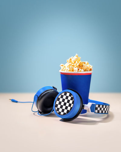 Composition with disposable cup with popcorn and headphones on a pink-blue background