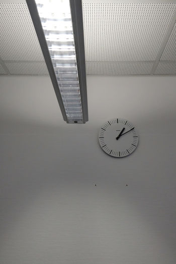 Low angle view of clock mounted on wall