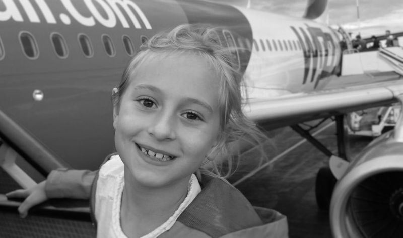 Beautiful girl boarding aircraft Looking At Camera Smiling Child Aircraft Flight Happy Black & White Desaturated