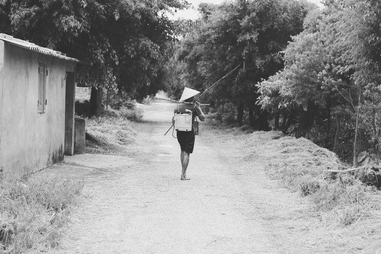 Rear view of fisherman walking on road