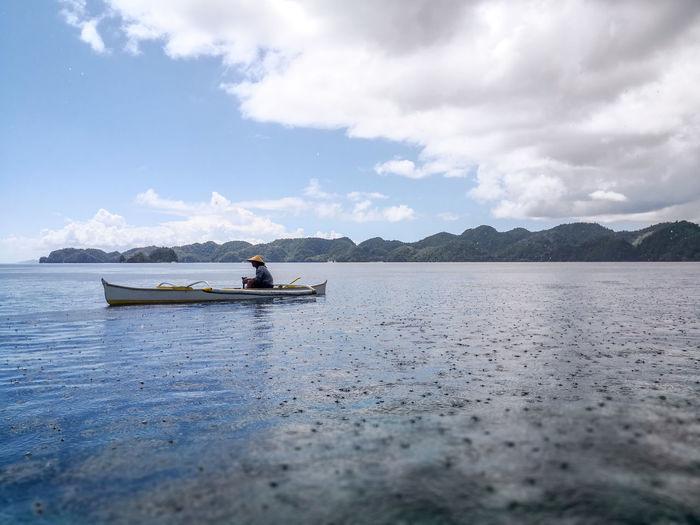 People on boat in sea against sky