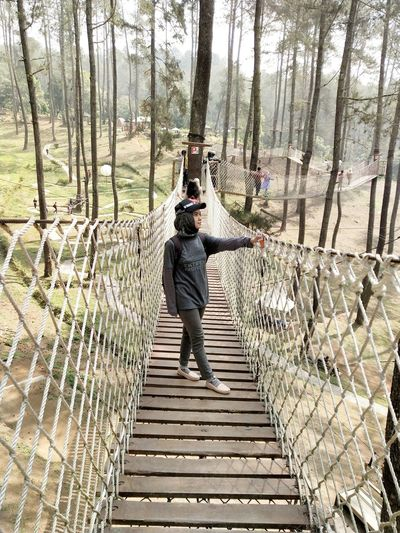 Full length of young man standing on footbridge