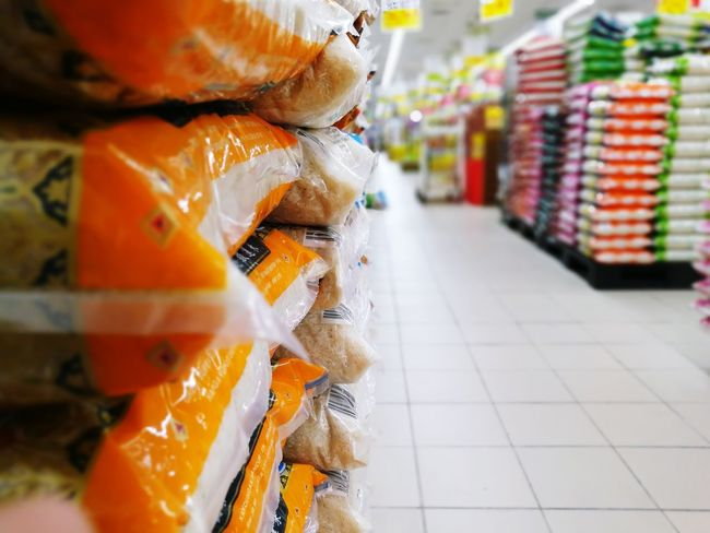 bags of rice stored in piles in supermarket Packaging Aisle Rice Supermarket Groceries Food Staple Store Retail  Consumerism Market Business Finance And Industry Close-up Passageway Produce Aisle