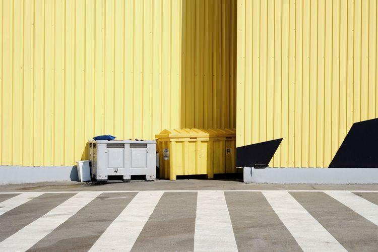Garbage bins against wall on street