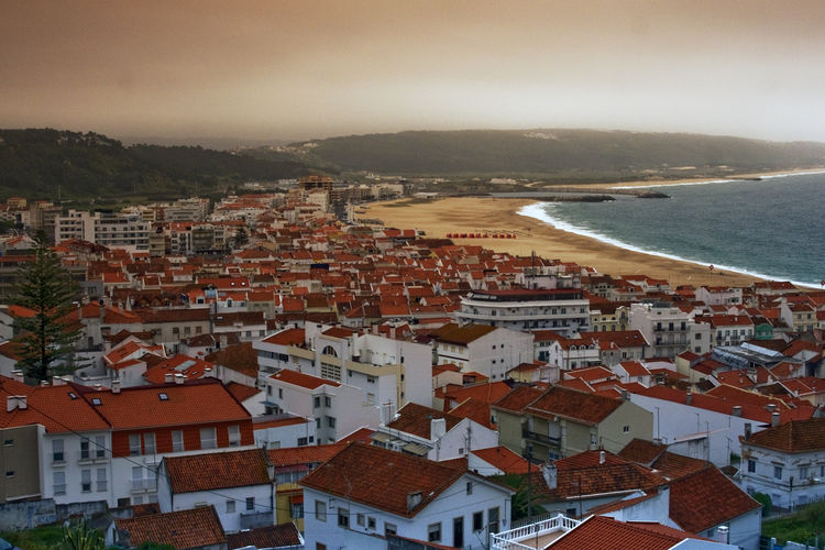 """Situated in the Portuguese Silver Coast, Nazare is a small fishing village in Portugal. Long an inspiration for many photographers and cinematographers, including a young Stanley Kubrik, Nazare has a very unique local culture intrinsically connected with the oceans with a long and rich sea tradition, embedded in local folklore. The Woman of Nazare ( Nazarena) for example, is the column that holds the community together and has been immortalised in monuments locally. When the men were at sea for months on end, the Woman of Nazare took care of family, business (usually selling fish and other sea produce) and everything else on land. This is even reflected in traditional attire. The """"7 skirts"""" (Sete Saias) for example, were in fact mostly work or utility aprons and shawls, exquisitely decorated and usually made by hand. When the men were returning from the sea with the catch, usually at night, the women would then be waiting on the beach and the aprons would turn to shawls becoming protective layers that they would wrap themselves with gradually as the cold set it. The sea was both the source of sustenance as well as of a lot of sorrow. Many women had lost husbands, sons and brothers at sea and many would trade in the colourful attire for black in mourning, a trait that it is still observed today. Some women continued their mourning to the end of their lives. Over the years, the fishing industry started to decline as both overfishing and the lack of interest of the younger generations in it, impacted local economy.. Nazare then turned to tourism as the main source of business, particularly in the Summer, season in which it is common for the locals to rent property to tourists over the summer (although nowadays, tourism is all year round, as Nazare became one of the best surfing destinations in the world, brought to world attention by surfer Garrett McNamara for it's 100ft waves at North Canyon, the deepest underwater canyon in Europe). While fishing is still part of th"""