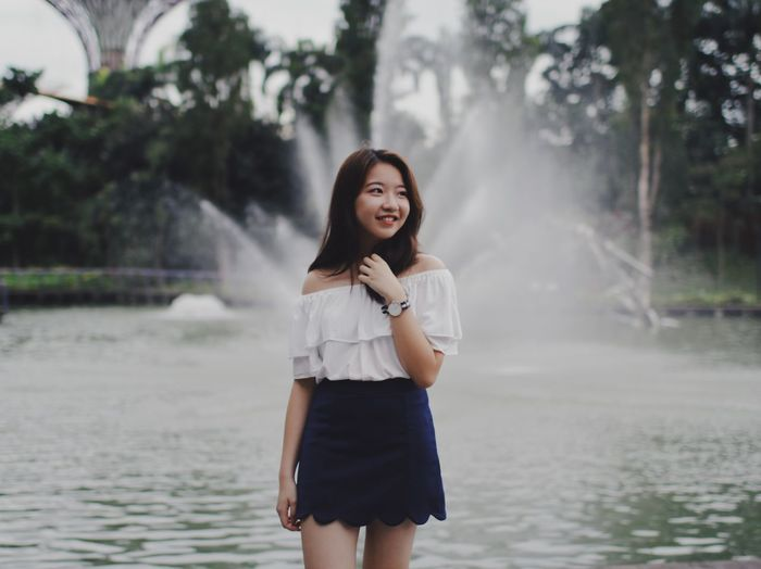 Smiling young woman standing against fountain at park