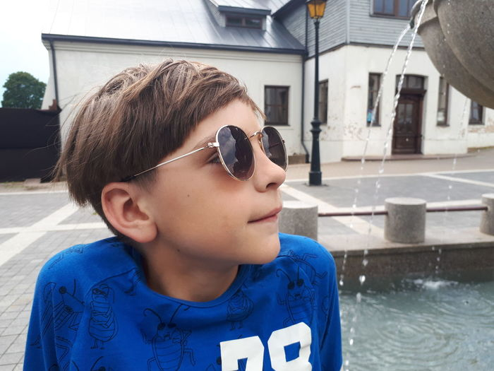 Boy wearing sunglasses against building