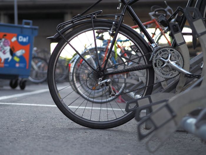 Close-up of bicycle parked on road in city