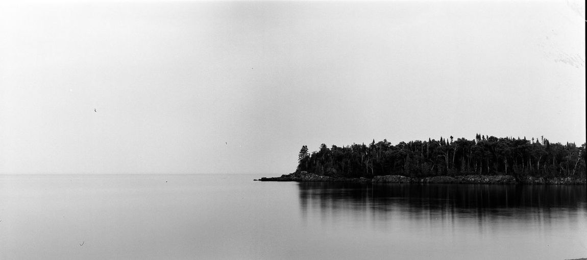 Lake Superior and Minnesota's north shore are pretty wonderful. Nature Tranquility Tranquil Scene Scenics Waterfront Beauty In Nature No People Sea Reflection Rock - Object Water Sky Outdoors Clear Sky Day Tree Horizon Over Water Lake Superior Analogue Photography Black And White Filmisnotdead Film Photography Minnesota Minnesotaphotographer Large Format
