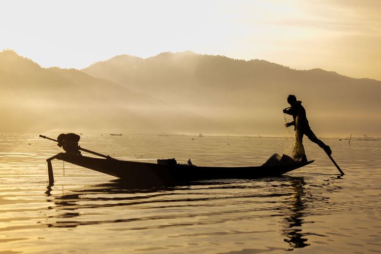 Early fisherman at Inle Lake. ASIA Asian Culture Beauty In Nature EyeEmNewHere Fisherman Fishing Inle Lake Lake Men Mode Of Transport Myanmar Nature One Person Real People Scenics Shadow Silhouette Sky Solitude Transportation Water