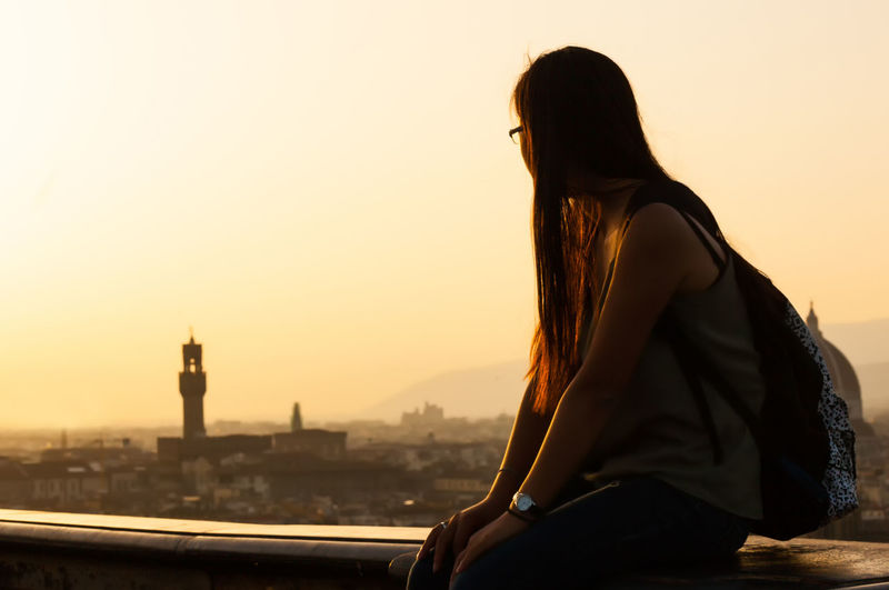 Woman sitting on building terrace in city against sky during sunset