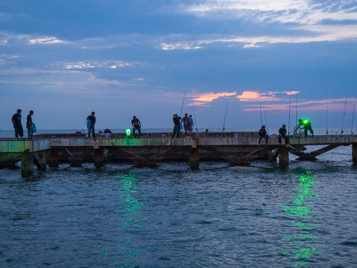 People fishing squids on abandoned construction site. Fishing Evening Green Light Group Poeple Thai Thailand Squids Sea