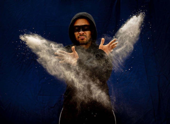 Man wearing hood with face paint throwing powder against backdrop