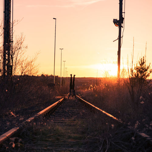 Sky Rail Transportation Sunset Nature Railroad Track Track Tree Plant No People Transportation Direction Land Sunlight The Way Forward Connection Sun Outdoors Silhouette Orange Color Field Electricity