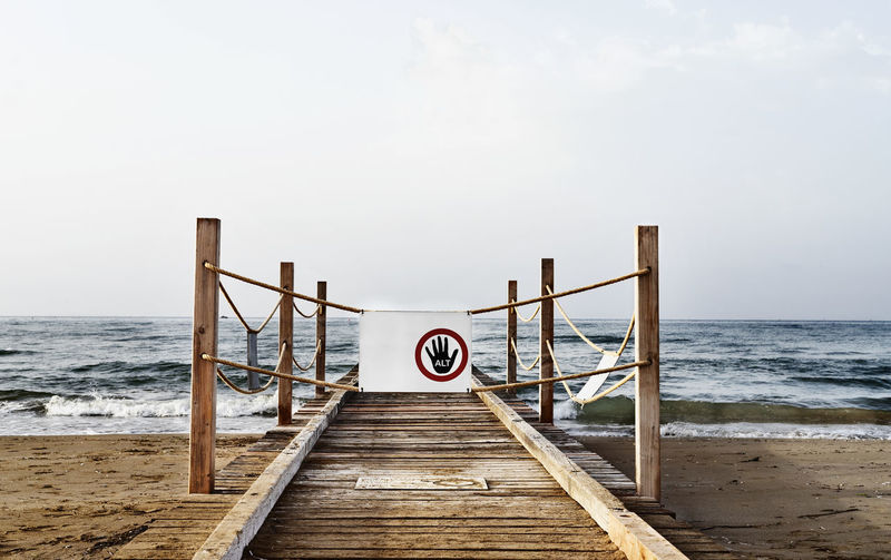 Wooden pier at the sea with danger sign -no access -