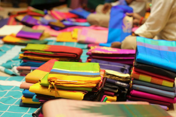 India Textile Industry Textiles Abundance Business Choice Close-up Collection Focus On Foreground For Sale In A Row Incidental People Indoors  Large Group Of Objects Market Market Stall Multi Colored Retail  Retail Display Sari Selective Focus Stack Still Life Table Variation