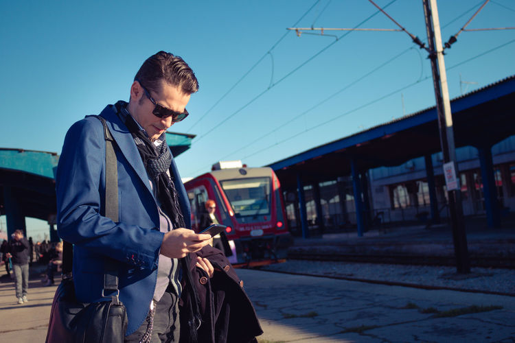 Mobile Phone Passenger Reading Social Networking Waiting Caucasian Cell Phone  Dialing Focus On Foreground Internet Lifestyles Men Mid Adult One Person Outdoors Railroad Station Platform Railway Station Smart Phone Standing Technology Text Messaging Train Station Typing Using Phone