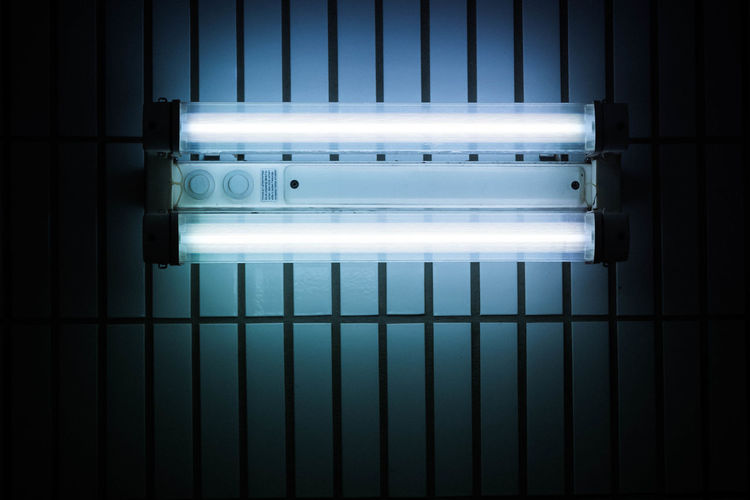 Low angle view of illuminated fluorescent light on ceiling