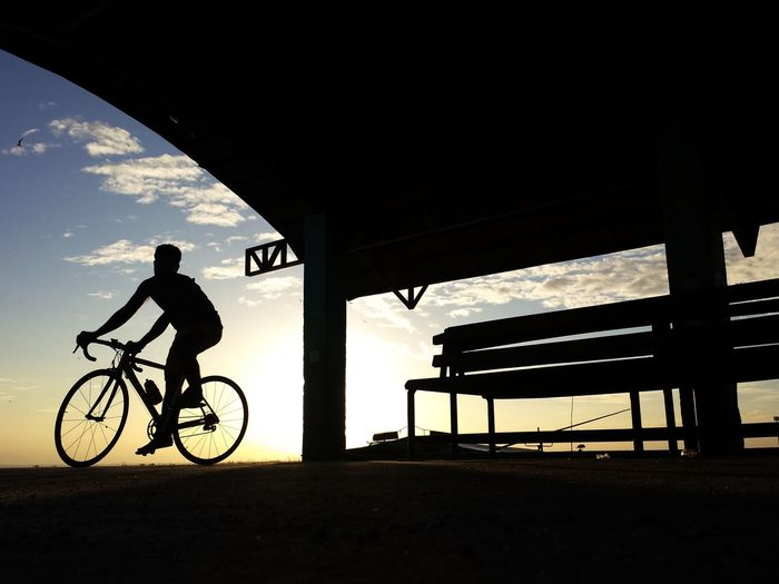 Silhouette cyclist riding bicycle at beach against sky during sunset