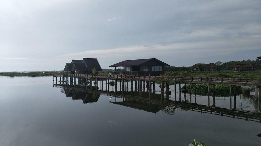 Stilt houses in lake against sky