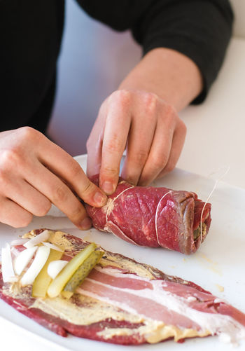 Close up of man's hands filling, rolling and tying together thinly sliced, raw beef roulades or Rouladen, a traditional German and Bavarian Sunday roast, filled with mustard, bacon, pickles and onions Bavaria Beef Cookies Cooking German Cuisine Hands Raw Raw Meat   Roulade Bacon Sunday Roast Beef Rolls Filling Franconia German Food Germany Man's Hands Meat Mustard Onion Onsions Pickle Rolling Rolls Uncooked
