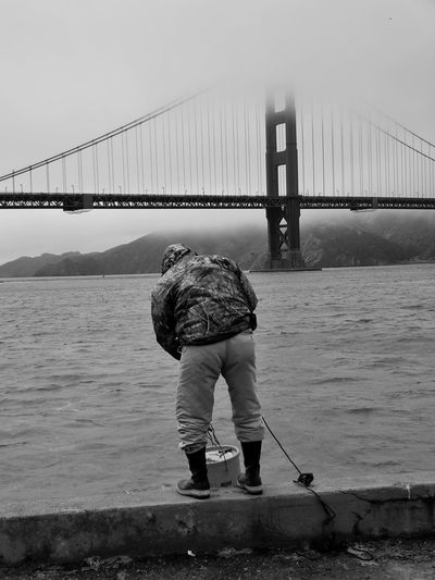 Rear view of man standing on retaining wall near golden gate bridge at harbor