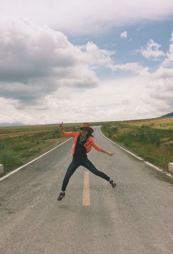 Playful Young Woman Jumping On Road Against Cloudy Sky