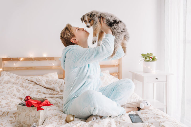 Young woman and dog sitting on bed at home