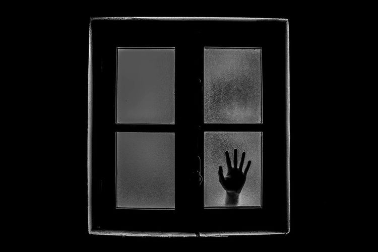 Cropped Hand Seen Through Closed Glass Window Of House