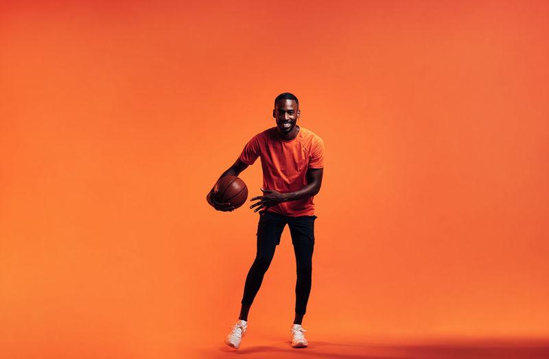 Full length of man standing against orange background