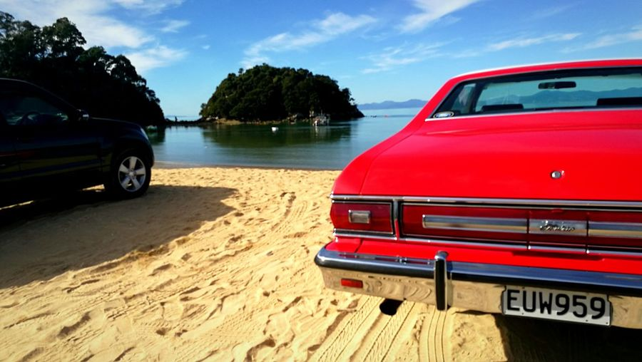 Standout red car Red Muscle Car American Automobile Water Beach Sea Red Sand Sky Vehicle Side-view Mirror Coastline Ocean