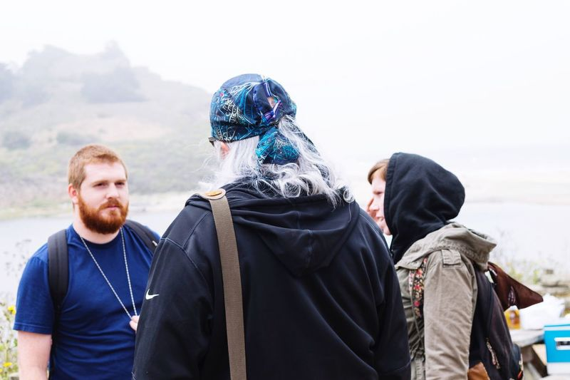 Friends hiking by mountain against sky during foggy weather