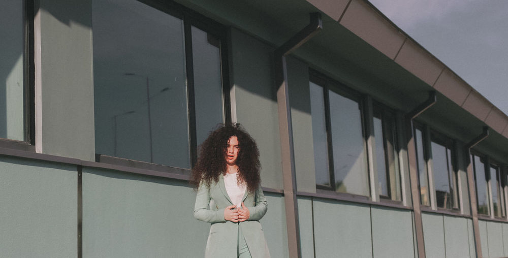Portrait of woman with curly hair standing against building
