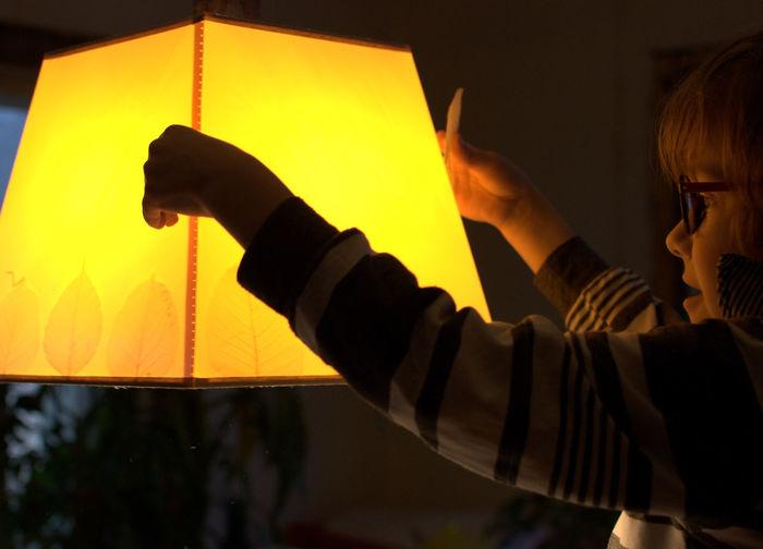 Side view of boy holding illuminated lamp shade