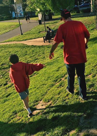 Fatherhood Moments Grass Full Length Casual Clothing Green Color Walking Togetherness Leisure Activity Rear View Lifestyles Shadow Sport Playing Field Green Person Grassy Cooperation Day Lawn Practicing